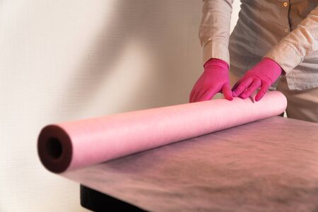 lays a disposable sheet on a massage couch