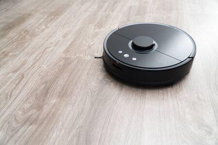 Robot vacuum cleaner black on the floor is cleaning, gray laminate Stock fotó