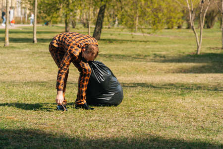 A young man in a mask is engaged in cleaning garbage in a park. pandemic environment concept.