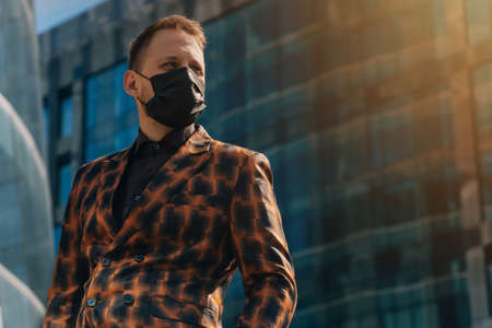young man in medical black mask looking away forward against the background of business center. midlle plan 免版税图像