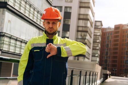a clean builder shows sincere emotions of indignation. A man in special clothes and a helmet shows dislike against the background of a ready made business center