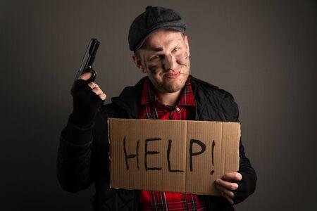 jeune voyou tenant une arme à feu et une pancarte demandant de l'aide. Le concept de hooliganisme au chômage.