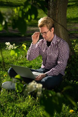 A young handsome man wears glasses to work behind a laptop. The concept of a freelancer has poor vision.
