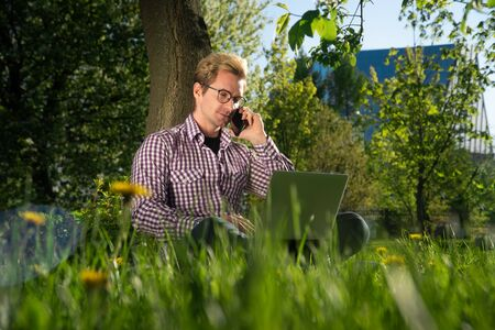 portrait of a young handsome caucasian man in a park. Freelancer is talking on a teleconference on a laptop. Online Meeting Concept