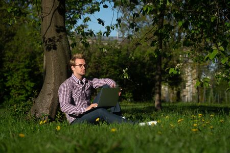 A young Caucasian man sits under a tree, typing on a laptop. Internet concept. Freelancer working in the park on the grass.