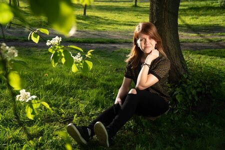 Portrait of young beautiful caucasian girl in a park sitting under a tree on a sunny day. concept of awalk in the park at sunset in summer.