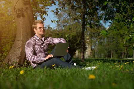 A young Caucasian man sits under a tree, typing on a laptop. Internet concept. Freelancer working in the park on the grass. on a sunny day Reklamní fotografie