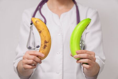 Close-up Nutritionist, young woman, nutritionist holding bananas in her hands. The concept of choosing fruits for proper nutrition for weight loss