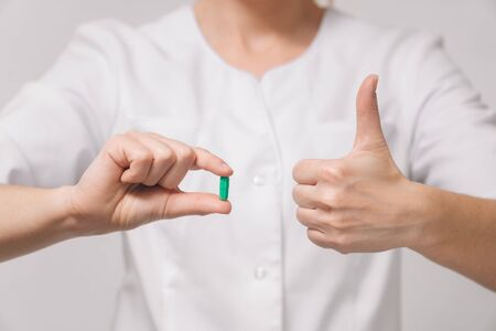 A girl doctor in a white robe holds a capsule pill with a closeup medicine for the disease. The concept of recovery