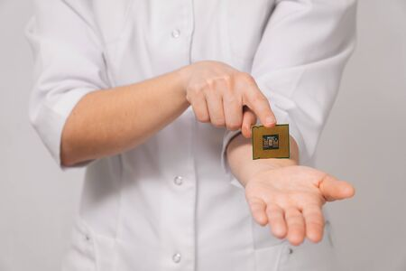 Close-up female doctor shows on her hand how to insert a microchip identification of people's data. The concept of innovation