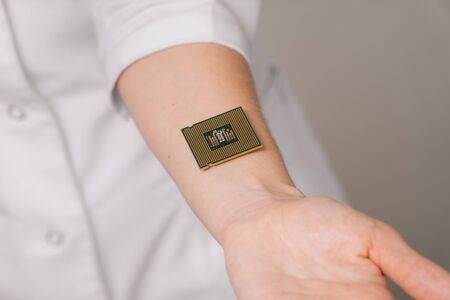 A female doctor shows on her hand how to insert a microchip identification of people's data. The concept of innovation.