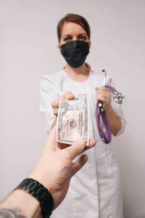 A woman doctor in a white coat takes cash from a patient. Bribery at work concept.
