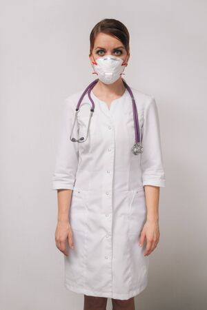 Young woman doctor in a respirator in a medical white coat a professional points to the side isolated on a light background