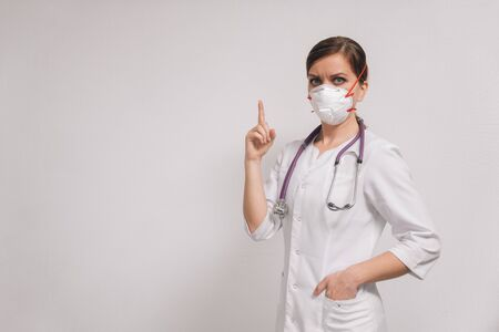 Young beautiful woman doctor in a medical mask in a white coat on a light background. Concept female hands show attention sign.