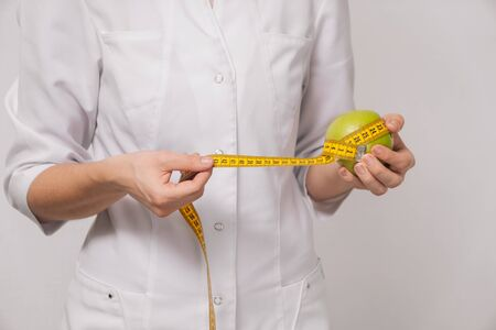 The nutritionist is a female nutritionist who measures the weight and volume of an apple's body. The concept of keeping an eye on your diet