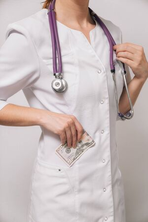 A woman doctor in a white coat puts cash in a pocket from a patient. Payment to a nutritionist for work. Bribery concept.