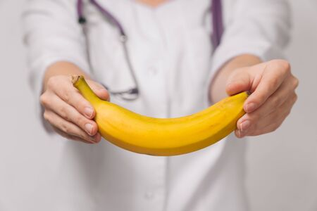 Close-up A nutritionist is a young woman, a nutritionist holds an overripe banana. The concept of choosing the right nutrition for weight loss Stock fotó