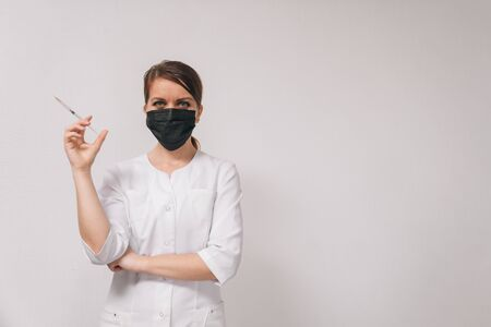 Young beautiful woman doctor in a medical mask in a white coat on an isolated white background holds an injection syringe. European doctor head shot concept.