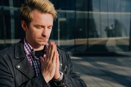Portrait of a young businessman who prays at a special time. Request for help appealing to God. Stock fotó