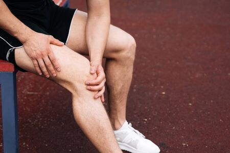 Close up athlete A man is holding on to his knee. Dislocation of the knee joint. The concept of falling during sports. Break your leg in training Stok Fotoğraf
