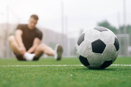 soccer player A man holds his foot. focus on the soccer ball. Dislocation or sprain of the joint. The concept of falling during sports. Break your leg in training