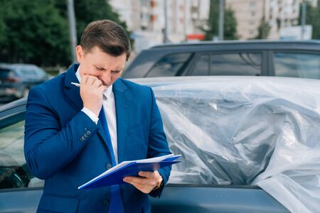 A man writes in a tablet next to the car. An accident on the road, the airbag didn't work. Accident, causing damage to a young man. Insur the car after the accident