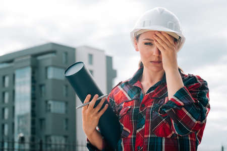 A brooding female builder with drawings of papers in her hands. Standard-Bild