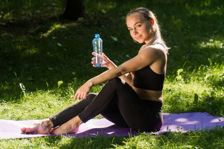 A beautiful girl holding a shaker with water. Concept Itnes trainer holds bottle for drinking time i trained