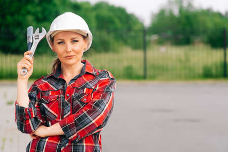 The brigadier is a young girl wistfully standing . A woman wearing a protective helmet. The concept of construction work. 免版税图像