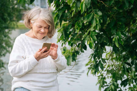 An adult woman speaks on a smartphone. An elderly grandmother holds a phone.
