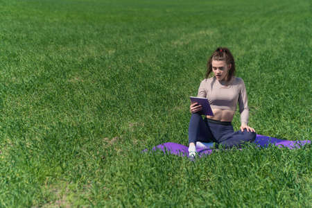 A young girl looks into a digital tablet against the backdrop of nature in a field. Stock fotó - 151141780