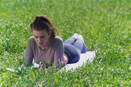 young girl lies on a sports mat on a summer day on the green grass. concept of yoga workouts outdoors Stock fotó - 151141790