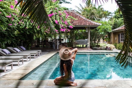 Young slim woman relaxing near pool with straw hat