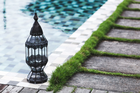 swimming candles: Vintage metal lantern near swimming pool