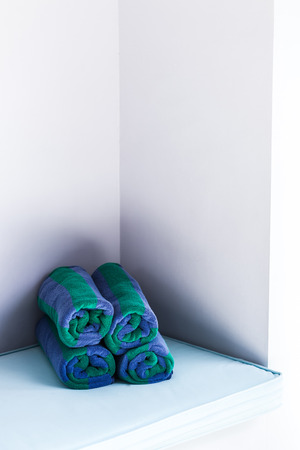 towels wall: Rolled multicolor pool towels near white wall
