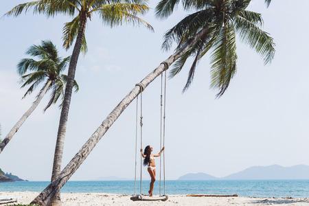 Beautiful thin woman swinging on a swing on paradise beach with nobody Stock Photo
