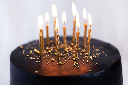 Noir gâteau d'anniversaire rond avec des bougies allumées d'or sur fond blanc