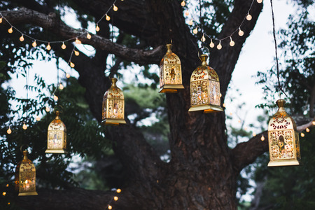 arching: Night wedding ceremony with a lot of candles and vintage lamps on big tree