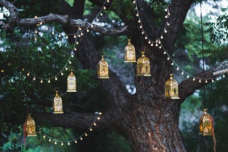 たくさんのキャンドルと大きな木のビンテージ ランプの夜の結婚式
