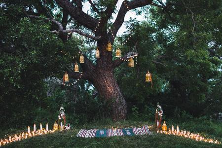 큰 나무에 촛불과 빈티지 램프의 많은 밤 결혼식