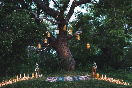 Night huwelijksceremonie met veel kaarsen en vintage lampen op grote boom