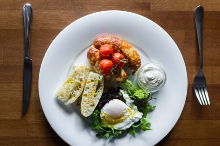 Breakfast with fried sausages, baked cherry tomatoes, poached egg and greens