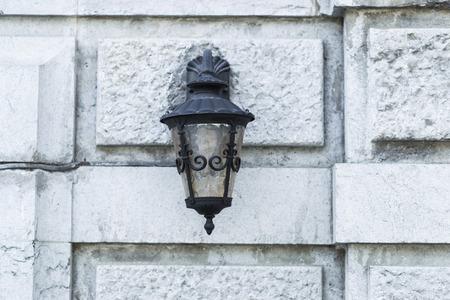 edad media: lámpara de hierro negro viejo sobre la pared de piedra del castillo medieval