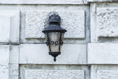 edad media: Old black iron lamp on stone wall of middle ages castle