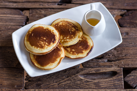 whole pecans: Delicious homemade pancakes with honey on a white plate