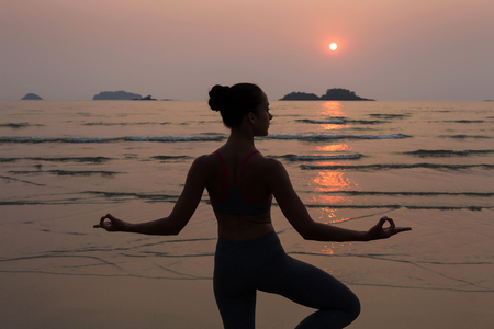 joga: Young slim woman practicing pose from yoga on the beach at sunset