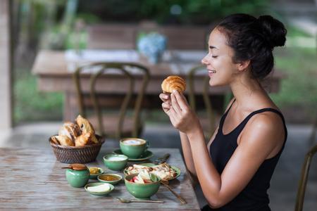 comiendo pan: mujer joven que tiene el desayuno y la celebración de croissant en la mano. La mañana de buen humor