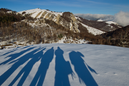 dint: People shadows on the snow in the mountains