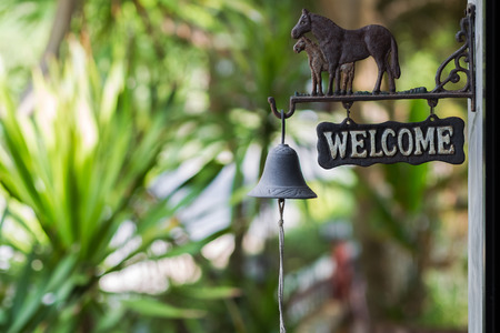 Vintage welcome plate with horses and bell in the garden