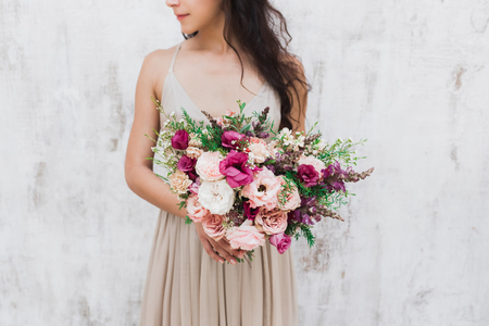 ?hic wedding bouquet of peonies and roses in hands of the bride